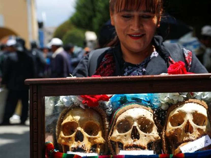 Bolivians decorate skulls with flowers and sunglasses to honour the dead