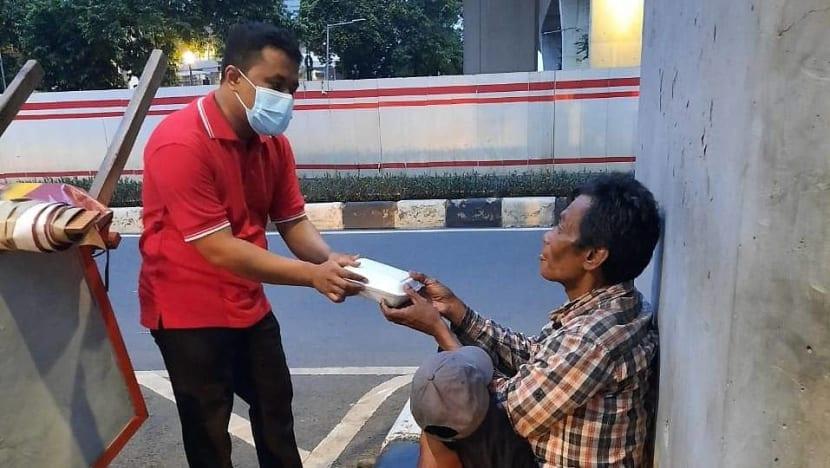 Dengan upah minimum, office boybagi-bagi makanan gratis kepada tunawisma di Jakarta